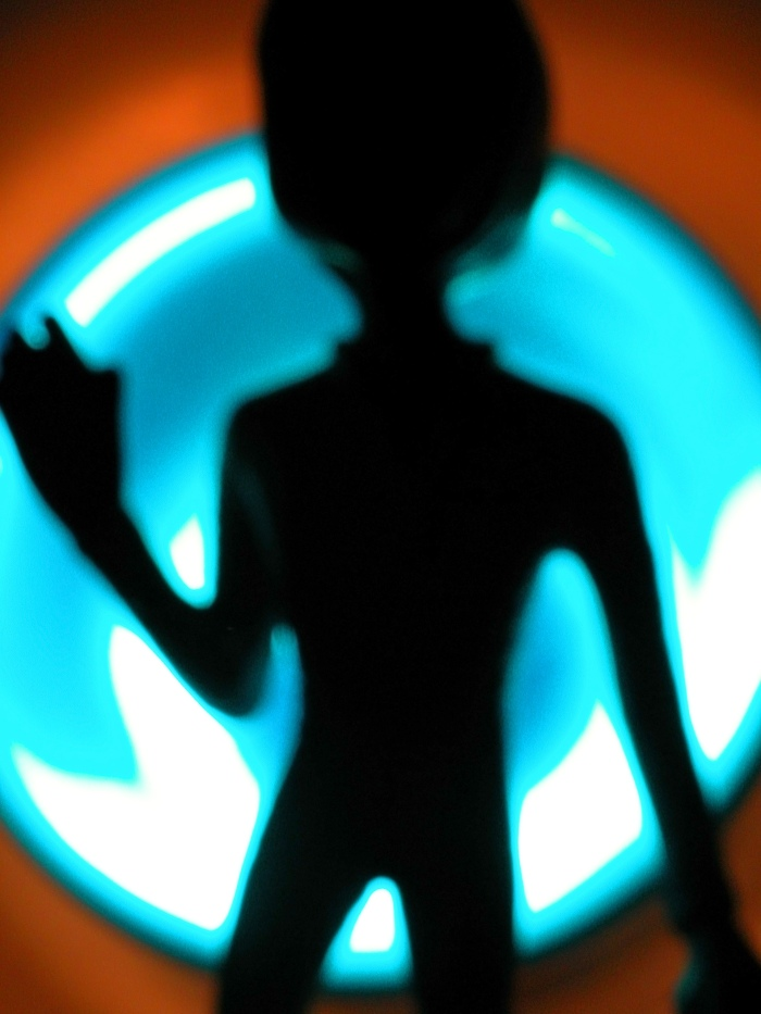 Image Description: The shadow of a being that seems alien. The background is a round, blue light.
