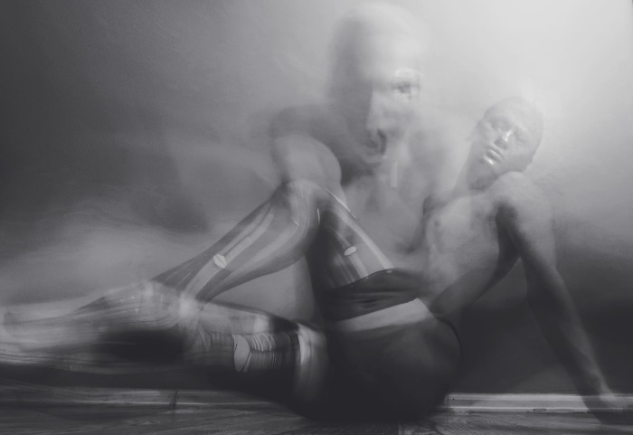 A black and white photo of a person lying on the ground wearing stockings.  A ghost-like image is overlaying the image and looks to be screaming.