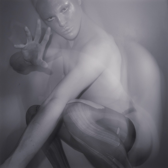 A black and white photo of a crouching person wearing shimmering make-up. They are wearing ripped stockings and reaching toward the camera.