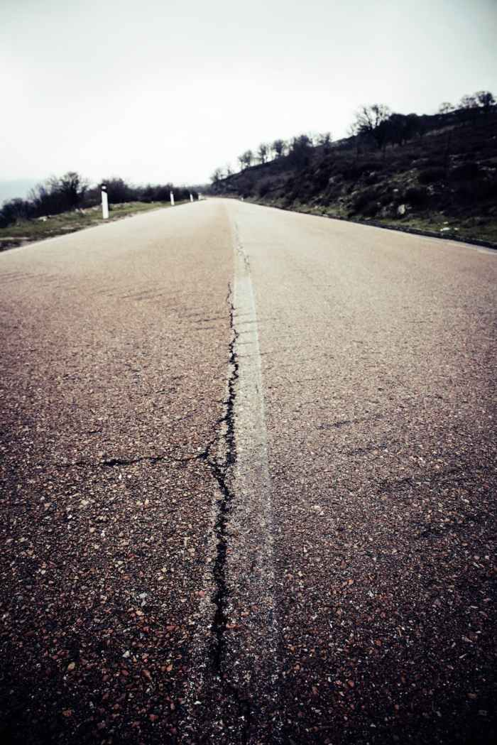 Image Description: Close-up of a paved, country road. A large crack runs through the middle of it.