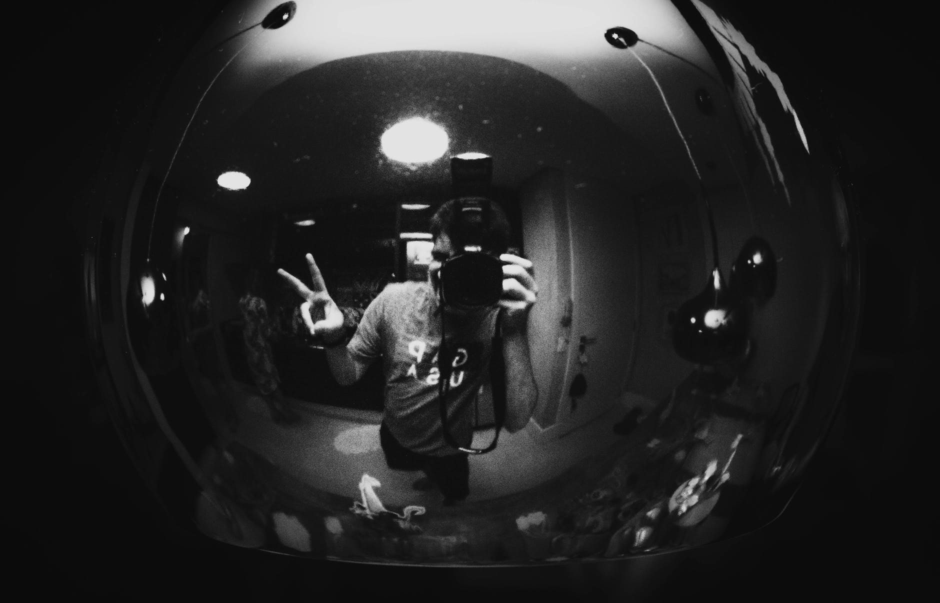 Image Description: A black and white photo of a man taking a selfie with his fingers in a peace sign.