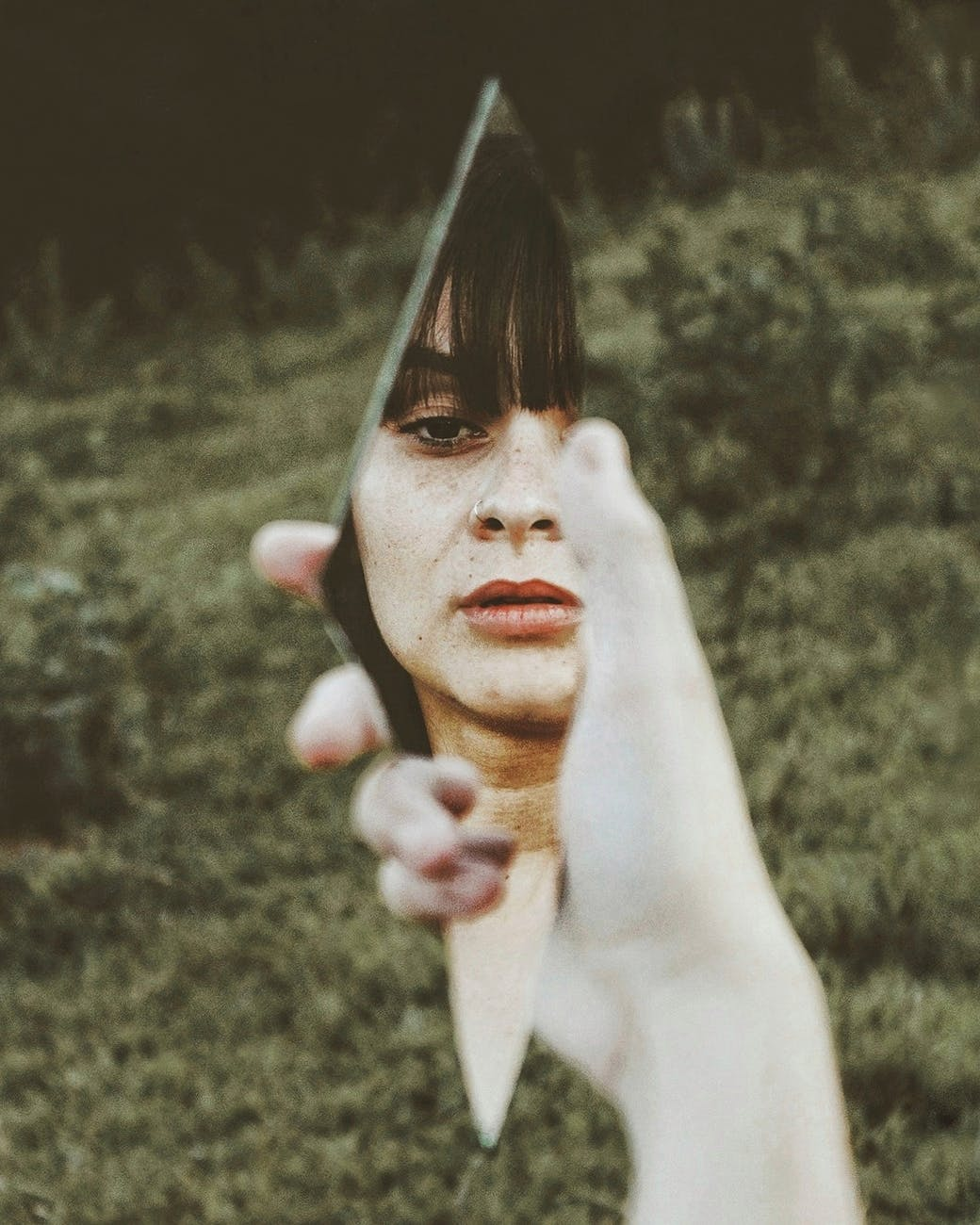 Image Description: A woman with brown bangs, a nose ring, and freckles looks at herself in the reflection of a piece of broken mirror.