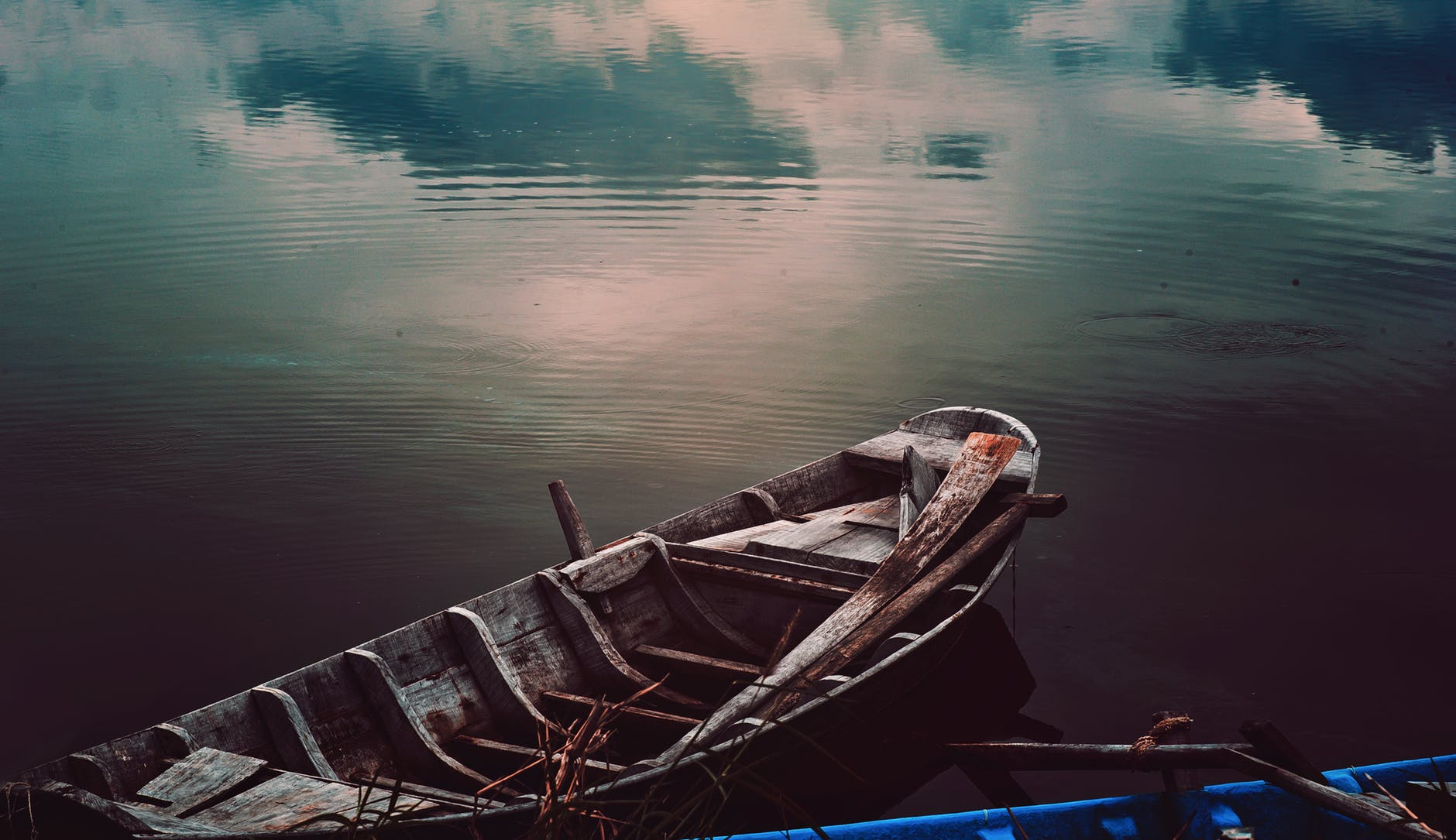 Image Description: A dreamy image of an old rowboat on a still lake. Clouds are mirrored in the water of the lake.