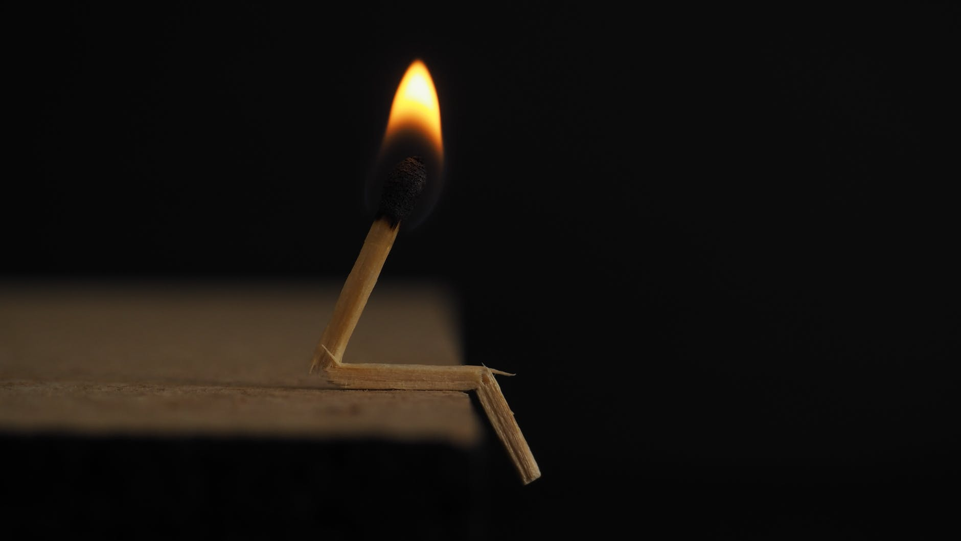 Image Description: A broken match is lit and sits at the edge of a table.