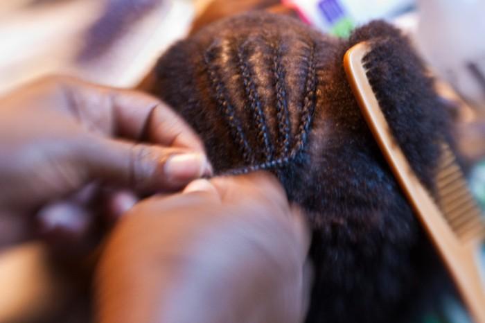 Image Description: Close-up of hands braiding cornrows into hair.