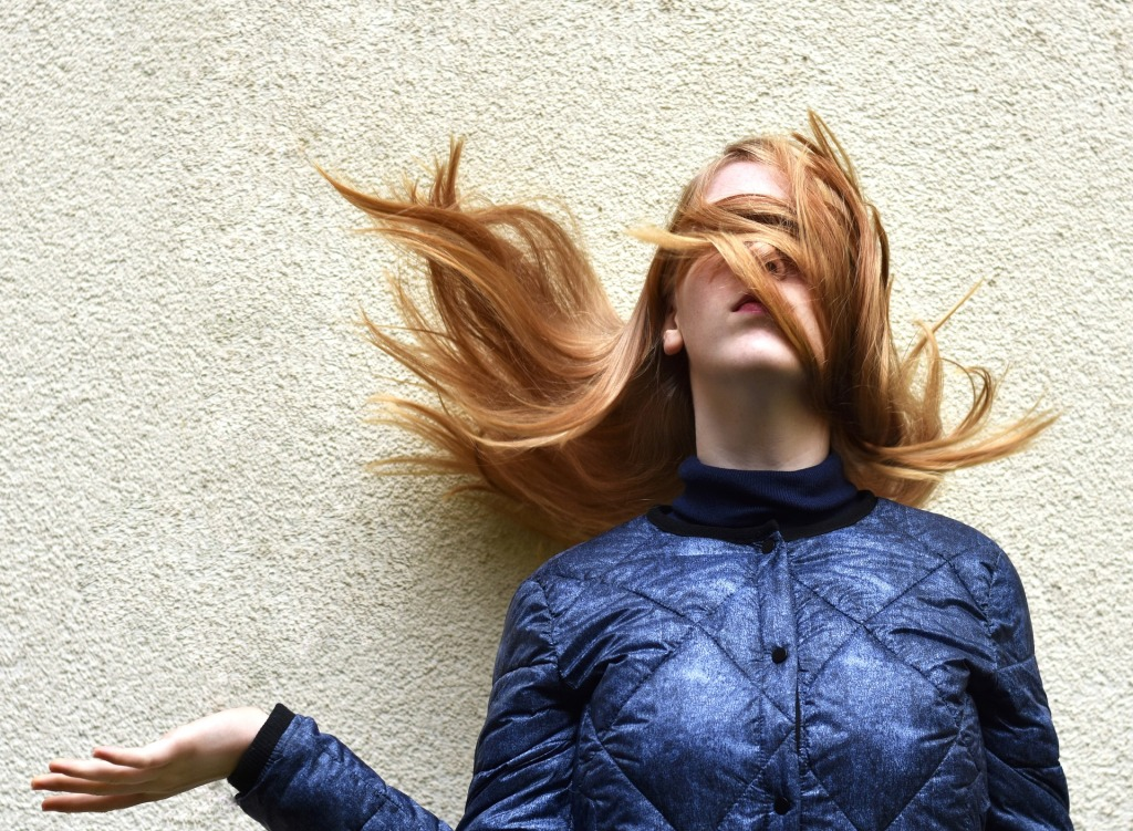 A woman stands against a white wall with her long hair blowing up around her face and covering her eyes. Her right arm is bent at the elbow with the palm upturned, as if waiting for something or asking a question.