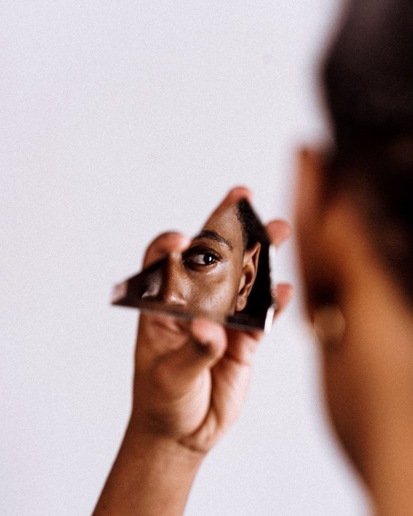 A black person (gender unknown) holds up a sliver of mirror that reflects a portion of their face.