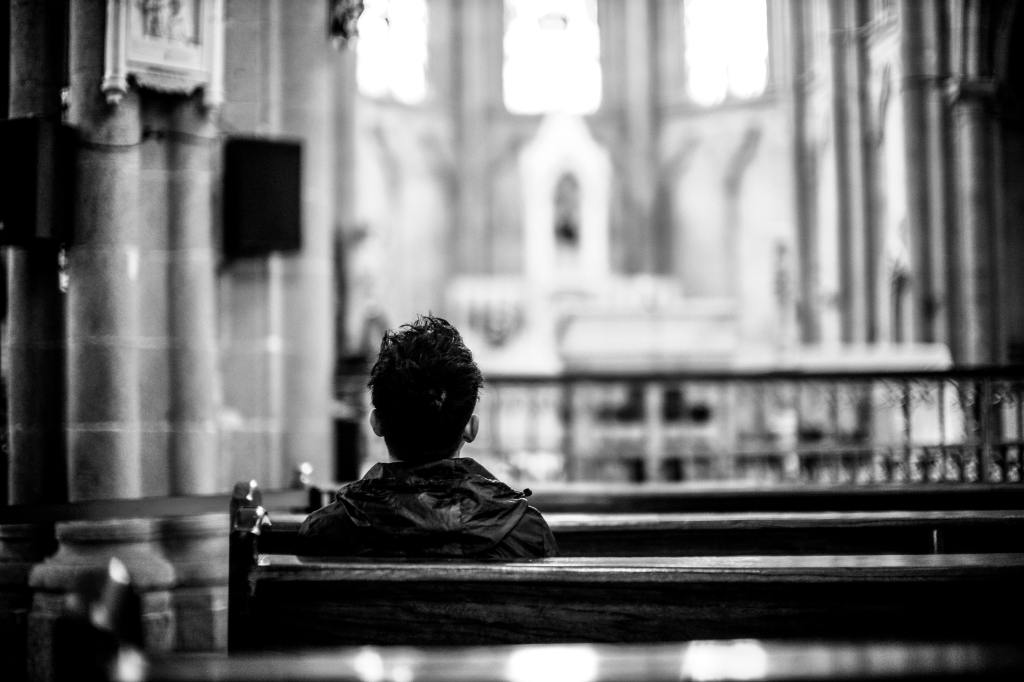 View from behind of a person with short hair and a jacket sitting in a church pew.