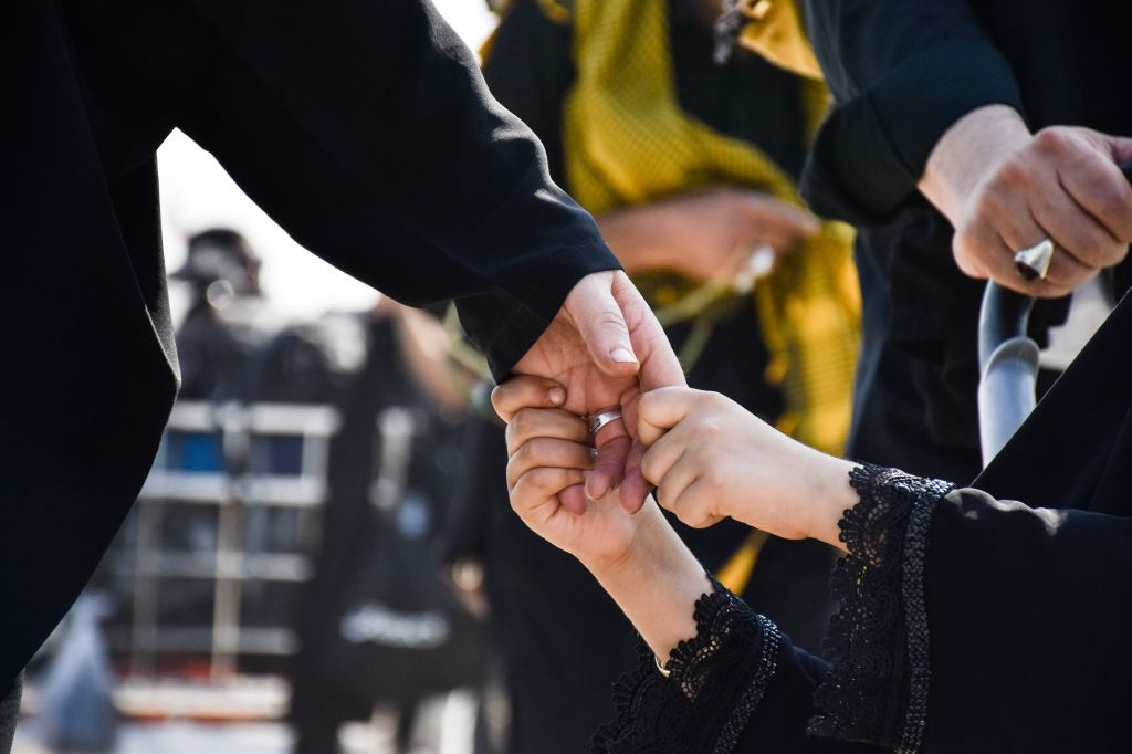 Close up of a child holding an adult's hand in a crowd of funeral goers.