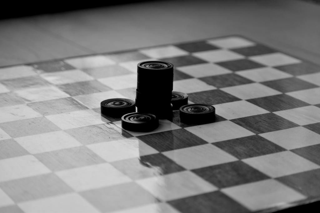 Descriptive image of checkers stacked on a game board.
