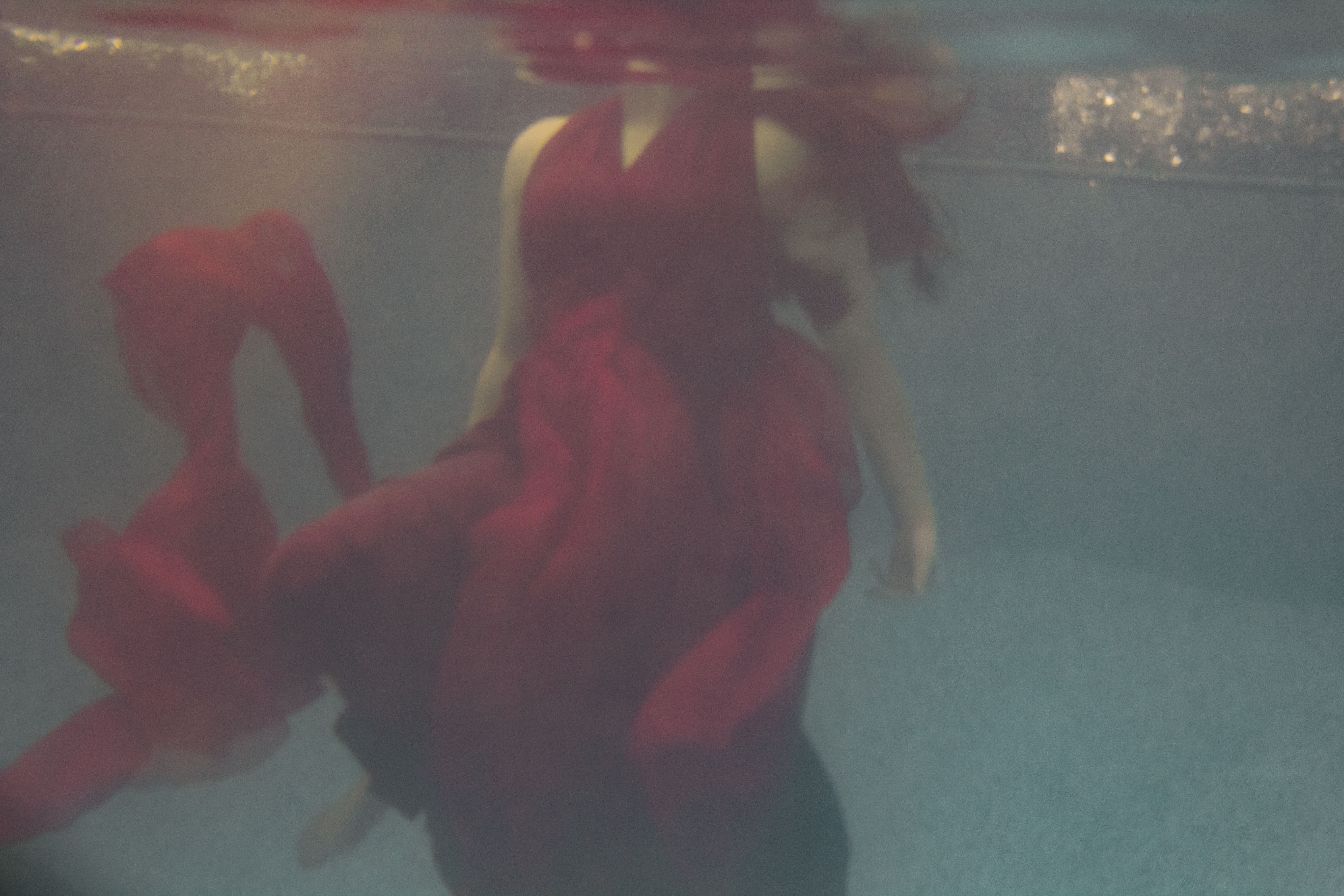 Underwater shot of a woman in a red dress, her head not visible above the surface.