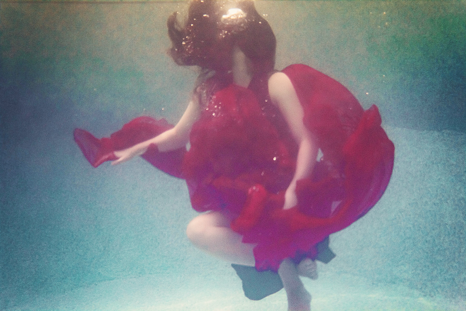 A woman in a red dress floats underwater. Her long hair covers her face as it rises towards the surface.