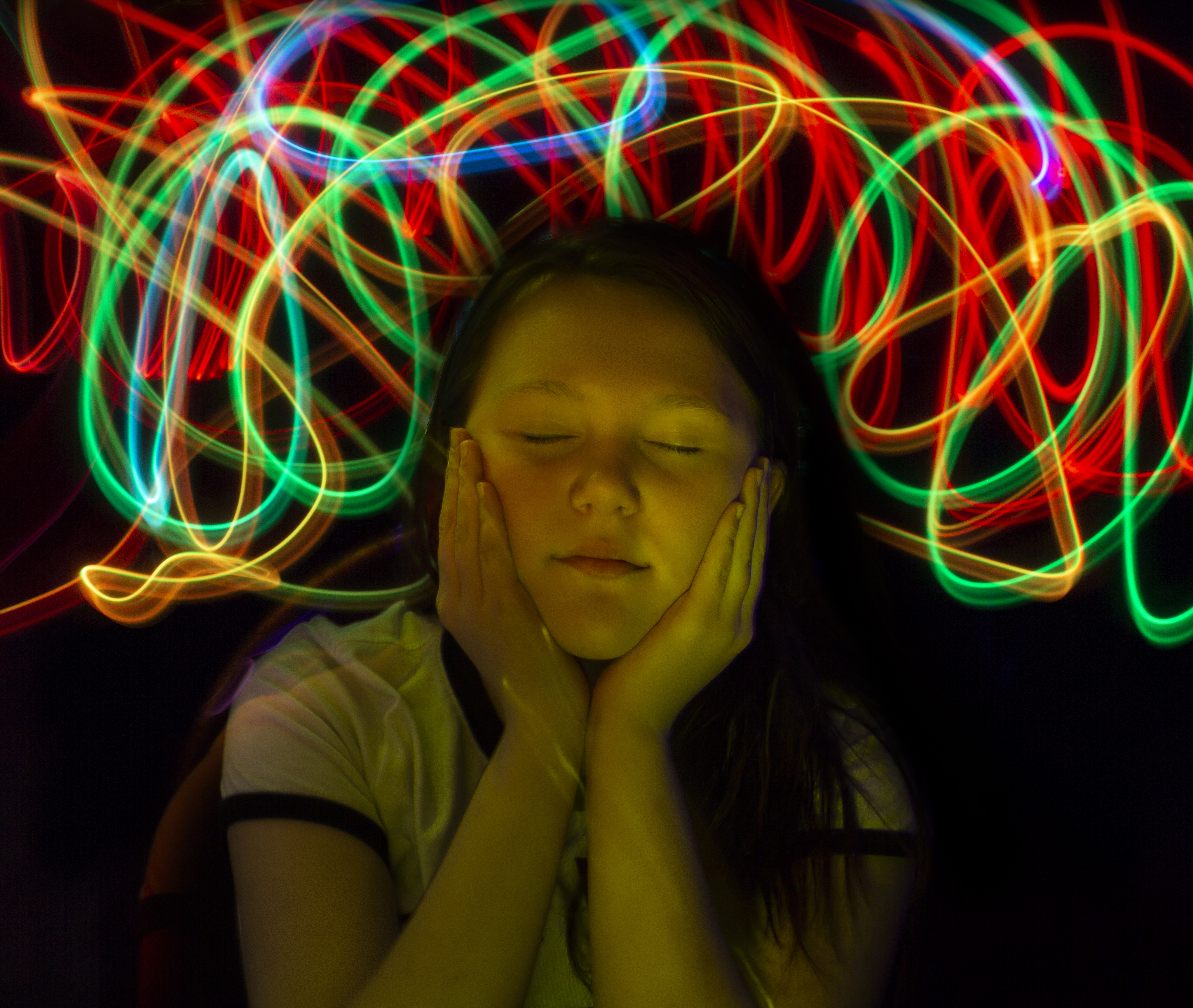 A girl with her eyes closed cups her cheeks with her hands in the dark under neon swirls.