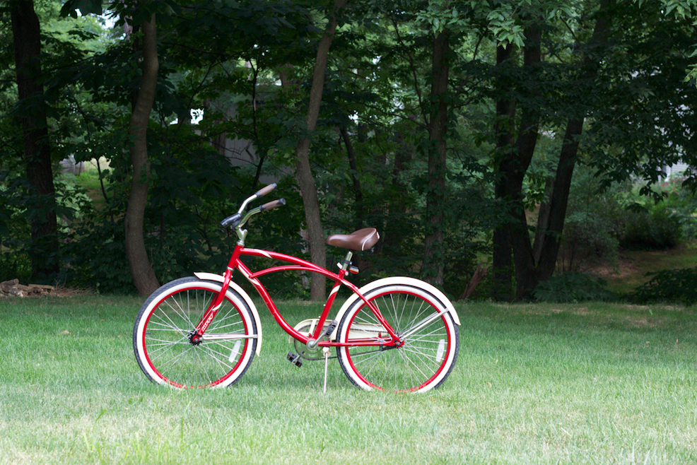 A red bicycle alone in a field.