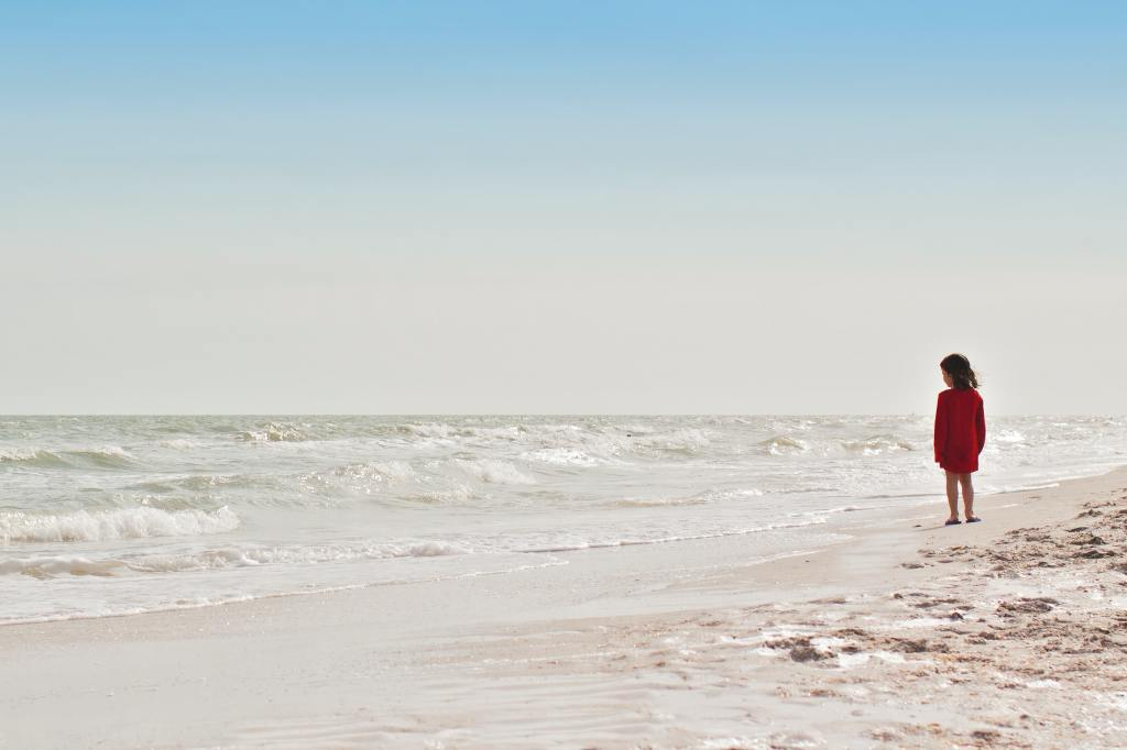 Descriptive image of a child on the beach looking at the surf.