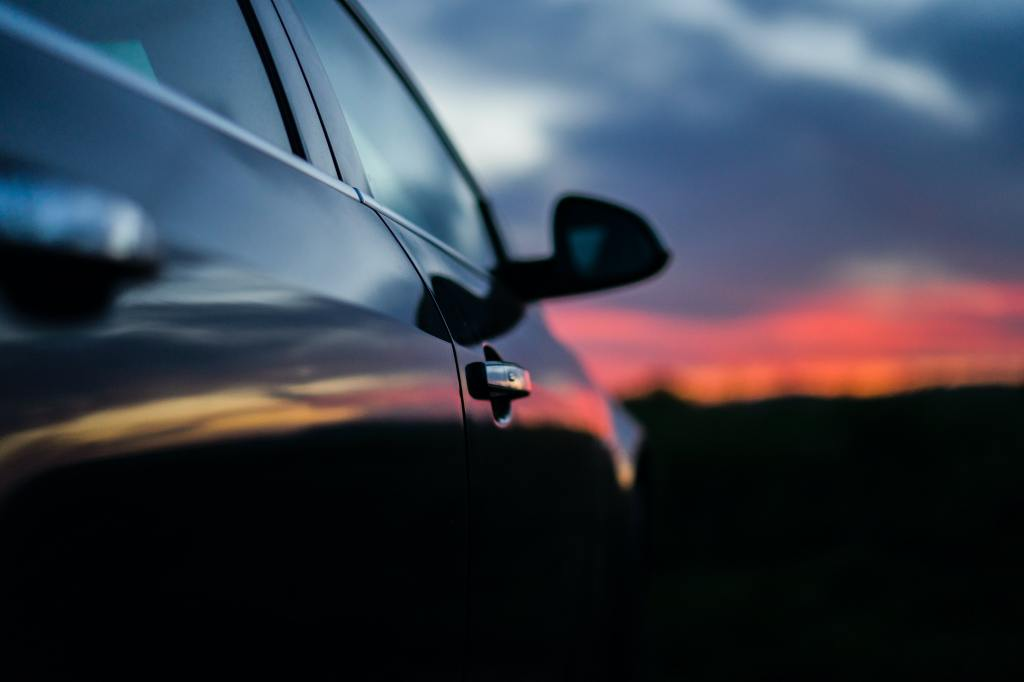 Descriptive image of a side of car during a sunset.
