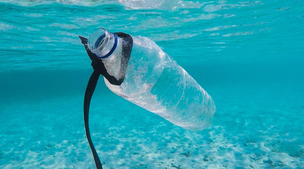 Plastic bottle underwater with a black ribbon.