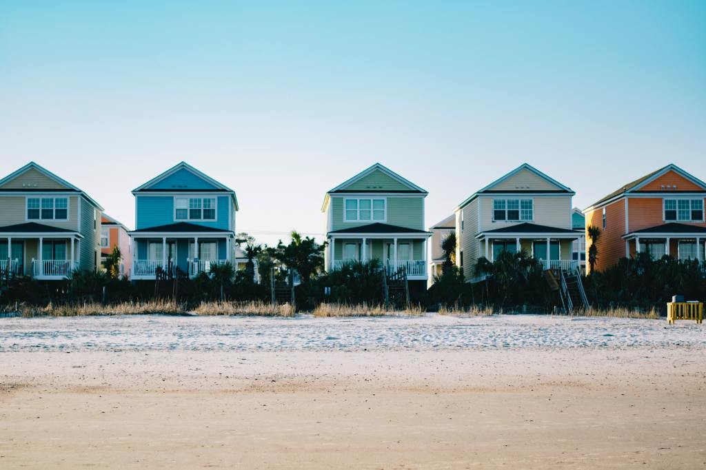 A row of beach houses of varying colors in the sun.